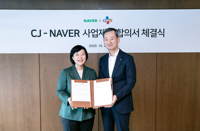 Naver CEO Han Seong-sook, left, and CJ's chief business strategy officer  Choi Eun-seok sign a strategic partnership deal Oct. 26