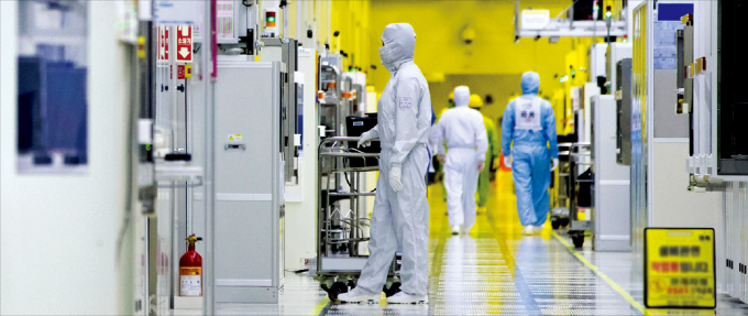 Samsung Electronics engineers check equipment in a clean room.