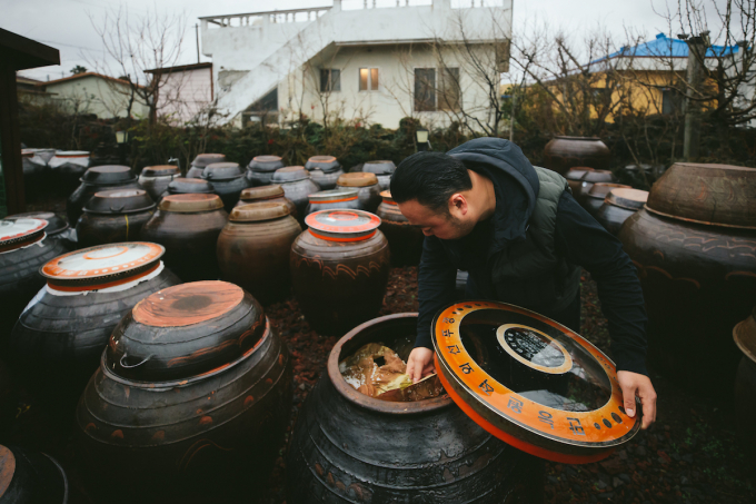 Chef Hooni Kim peers into a clay jar containing Doenjang.  (Photo by Kristin Teig)