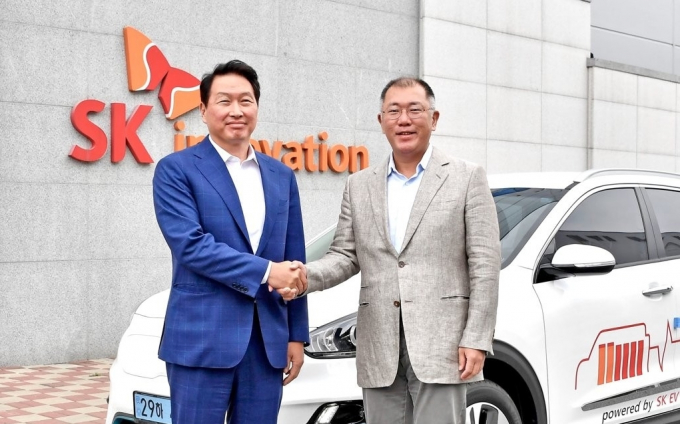 Hyundai Motor Group Chairman Chung Euisun (right) and SK Group Chairman Chey Tae-won shake hands after signing an MOU on hydrogen projects.