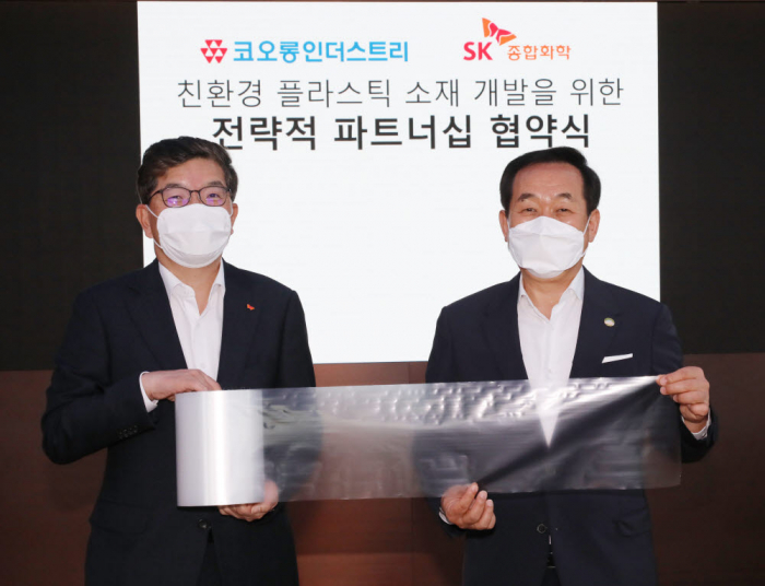 SK Global Chemical CEO Na Kyung-soo (left) and Kolon Industries CEO Jang Hee-goo (right) hold a PBAT sample at their strategic partnership signing ceremony. (Courtesy of SK Innovation)