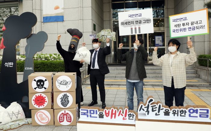 Environmental activists stage a performance outside a Seoul office building on Apr. 20 to protest NPS investment in coal-related companies.