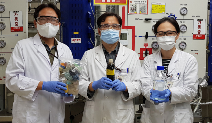 SK Innovation researchers hold samples of pyrolysis oil and insolvent made of waste plastic (Courtesy of SK Innovation)