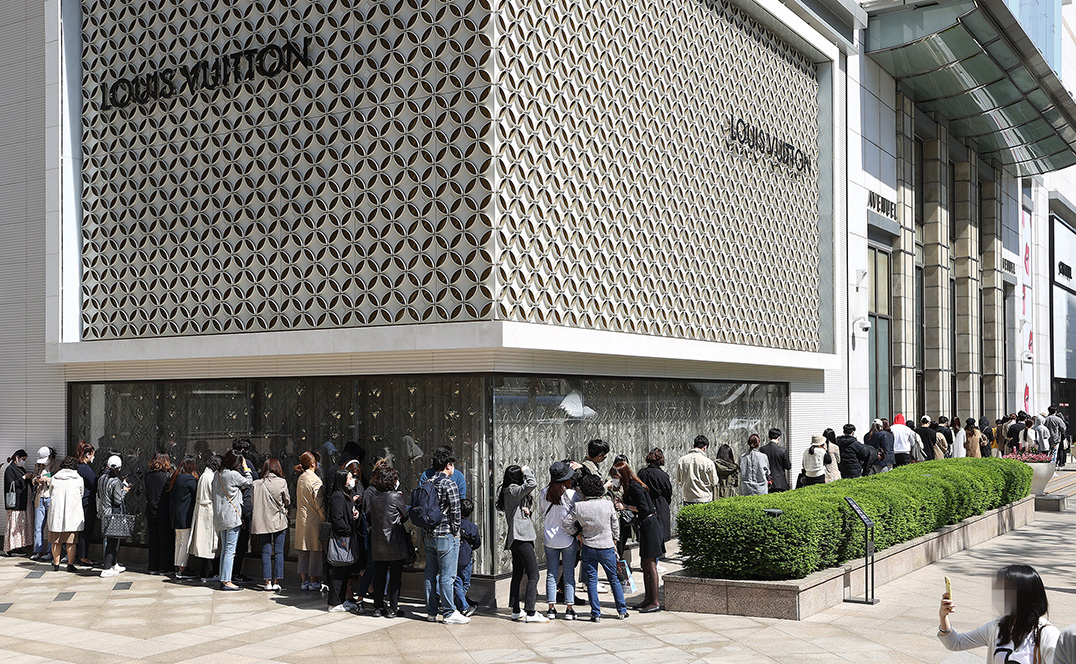 A long line of customers wait outside the Louis Vuitton store of Lotte Department Store's main branch